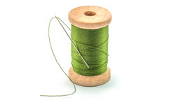 Isolated wooden spool of green thread and needle. Isolated wooden spool of green thread with a needle stock photo