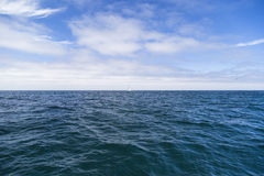 Isolated yacht sailing in the blue Atlantic Ocean near Monterey, California Royalty Free Stock Photo