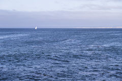 Isolated yacht sailing in the blue Atlantic Ocean near Monterey, California Royalty Free Stock Images