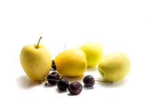 Isolated yellow apples and black cherries Royalty Free Stock Photos