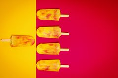 Isolated yellow-red ice cream on a colorful background. Isolated delicious yellow-red ice cream on a colorful summer background royalty free stock photo