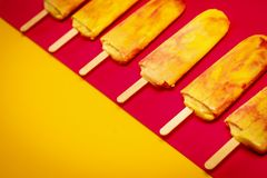 Isolated yellow-red ice cream on a colorful background. Isolated delicious yellow-red ice cream on a colorful summer background royalty free stock images