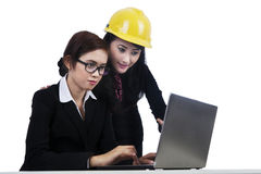 Isolated young architects working on a laptop Stock Images