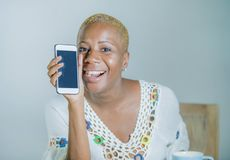 Isolated young attractive and happy black afro American woman ho. Lding tea or coffee cup using internet social media app on mobile phone smiling cheerful and stock photography