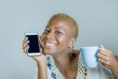 Isolated young attractive and happy black afro American woman ho. Lding tea or coffee cup using internet social media app on mobile phone smiling cheerful and royalty free stock photos