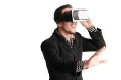 Isolated young businessman with virtual reality glasses. Isolated close up of smiling businessman in a formal wear and virtual reality glasses who trying to Royalty Free Stock Photo