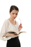 Young girl eye glasses rim at mouth reading book I. Isolated young girl eye glasses rim in her mouth reading book Royalty Free Stock Photos