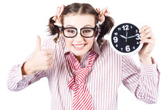 Isolated Young Girl Showing Clock With Thumbs Up. Young Girl In Red Striped Business Shirt And Tie Showing Time On Clock With Thumbs Up In A Depiction Of Good Royalty Free Stock Photo