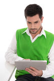 Isolated young handsome man is looking at tablet pc on white. Stock Images