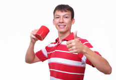 Isolated young man with red coffee cup. Isolated portrait of a young man with red coffee cup and thumb up Royalty Free Stock Image