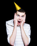 Isolated Young Man At A Surprise Birthday Party. Shocked Looking Young Man With Party Hat In A Surprise Birthday Concept Isolated On Black Background Stock Image