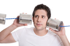 Isolated young man in white holding tin can. Communication or de Stock Images