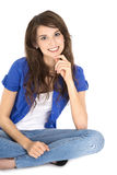 Isolated young pretty smiling teenager sitting with crossed legs. Royalty Free Stock Photos