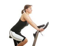 Isolated young woman sitting on a spinning bicycle. Isolated young womanexercising on a spinning bicycle - profile Royalty Free Stock Photos