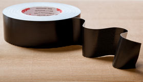 Isolating tape. Black isolating (dielectric) tape on neutral background stock image