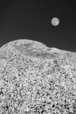 Isolation. Black and white close-up of rock with moon in background, vertical Stock Photography