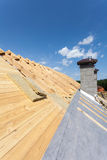 Isolation de toit Nouvelle maison en bois en construction avec des cheminées contre le ciel bleu Photographie stock