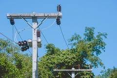 Isolation en céramique pour le câble électrique accrochant sur le pylône électrique avec le fond de ciel bleu Photos stock