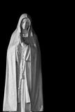 Isolation of religion. Religious statue isolated on black background stock photography