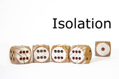 Isolation, symbolic scene. With four similar dices, standing close to each other and a different one standing alone in the distance Stock Photography
