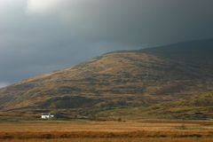 Isolation. A white farmhouse illuminated by a low sun after the storm passes in the Scottish Highlands Stock Image