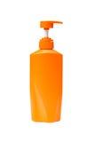 Isolato arancio della bottiglia della pompa di colore di plastica della testa fotografia stock