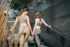 Isolato su bianco Due giovani donne in abiti sportivi stanno ai livelli della città, i punti, resto dopo la formazione Le ragazze Fotografie Stock