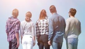 Isolato su bianco un gruppo di giovani che esaminano lo spazio della copia Immagine Stock
