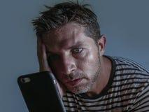 Isolato vicino sul ritratto del fronte di giovane uomo attraente e sollecitato facendo uso della sensibilità del telefono cellula immagini stock