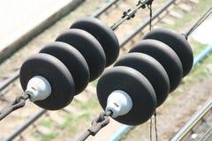 Isolatorer på järnväg trådar arkivbild