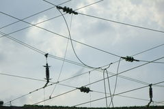 Isolators of a high-voltage power line. With a cloudy sky Stock Photo