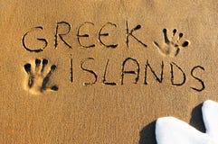 Isole greche scritte sulla spiaggia sabbiosa Fotografia Stock