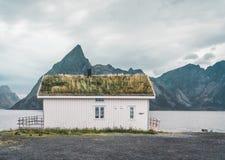 Isole Norvegia di Lofoten - settembre 2018: Camera con il tetto e le montagne tradizionali dell'erba nei precedenti su un nuvolos fotografia stock