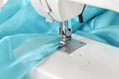 Isoleer over wit Het naaien proces, het stikken van een modieuze blauwe kleding of het gordijn van Tulle Stock Foto