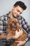 Isoleerde de knappe jonge hipstermens van het close-upportret, die zijn goede vrienden rode hond kussen lichte achtergrond Positi Royalty-vrije Stock Foto