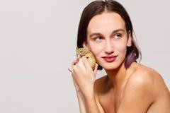 isolement Une belle fille avec les cheveux courts tenant un gecko d'iguane dans sa main et la pressant à son visage inside photographie stock