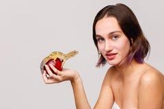 isolement Une fille aux cheveux foncés avec les cheveux courts se tient dans sa main une pomme rouge sur laquelle repose un gecko image stock