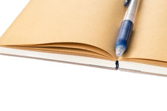 Isolerad öppen brun anteckningsbok med den blåa kulspetspennan Royaltyfri Foto