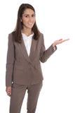 Isolerad affärskvinna i brunt som framlägger och visar med handen Royaltyfri Foto