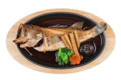 Isolerad bästa sikt av Fried snapper med rädisan, moroten, shiitaken och choy summa i varm platta på träplattan Royaltyfri Foto