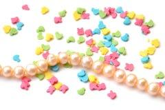 Isolerad bakgrund av ljus konfekt som överträffar i form av djur och rad av pärlor av rosa pärlor för hav på vit arkivfoto