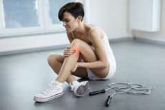 isolerad benwhite för bakgrund skada Härlig kvinnakänsla smärtar i knäet, smärtsamt knä royaltyfria bilder