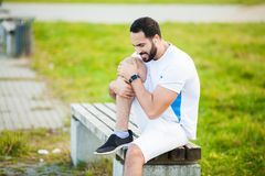 isolerad benwhite för bakgrund skada Manligt idrottsman nenlidande från smärtar i ben, medan öva utomhus arkivbilder