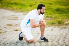 isolerad benwhite för bakgrund skada Manligt idrottsman nenlidande från smärtar i ben, medan öva utomhus arkivfoton