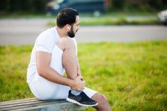 isolerad benwhite för bakgrund skada Manligt idrottsman nenlidande från smärtar i ben, medan öva utomhus arkivfoto