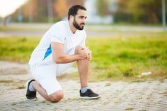 isolerad benwhite för bakgrund skada Manligt idrottsman nenlidande från smärtar i ben, medan öva utomhus royaltyfria foton