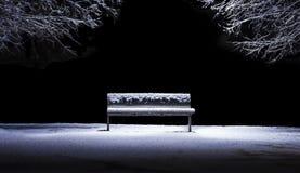 Isolerad bänk i en parkera efter ett snöfall Arkivfoto