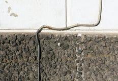 Isolerad elektrisk tråd på sten- och murbrukväggen Arkivbild