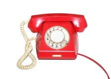 Isolerad gammal röd telefon Arkivfoto