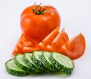 Isolerad grön gurka, röd tomat på en vit bakgrund Fotografering för Bildbyråer